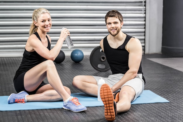 Couple assis sur un tapis de fitness au gymnase de crossfit