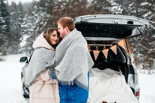 Un couple assis avec des tasses à l'arrière d'une voiture et un pique-nique dans une forêt de neige