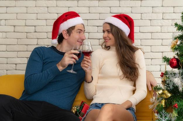 Couple assis en train de boire du vin rouge sur le canapé.