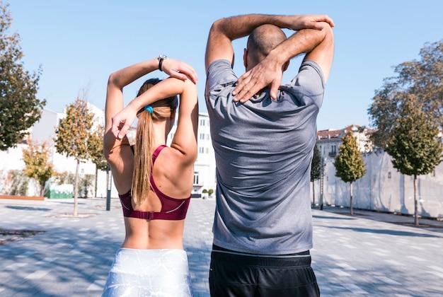 Couple, athlète, étirer, elle, mains, debout, dehors