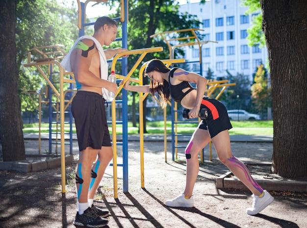 Couple d'athlètes caucasiens avec bande élastique de kinésiologie sur les corps, bel homme avec une serviette sur l'épaule et l'eau et femme brune à l'aide d'haltères au terrain de sport.