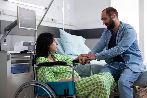 Un couple attend un enfant dans une salle d'hôpital en train de parler