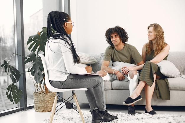 Couple en attente lors d'une réunion de conseil à domicile. psychologue de visite de couple pour des conseils relationnels.