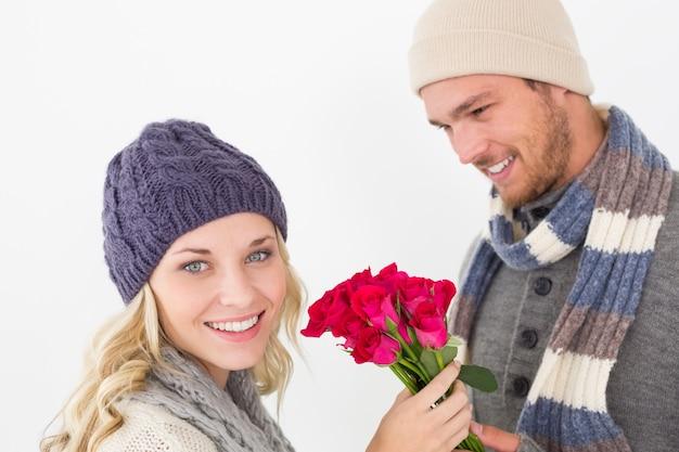 Couple attractif dans des vêtements chauds, tenant des fleurs