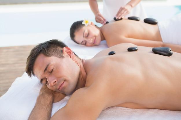 Couple attrayant bénéficiant de massage aux pierres chaudes au bord de la piscine