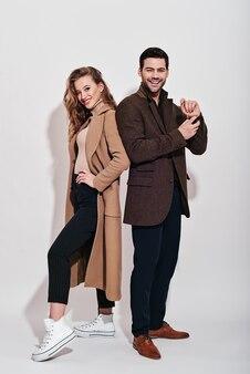 Couple attrayant et bien habillé ludique qui pose en studio souriant et debout sur fond gris