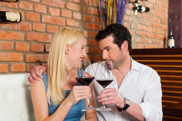Couple attrayant, boire du vin rouge au restaurant ou au bar