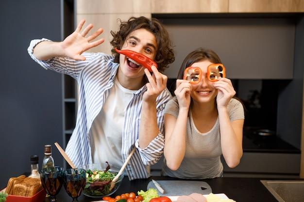 Couple attrayant joyeux avec le poivron rouge sous les yeux