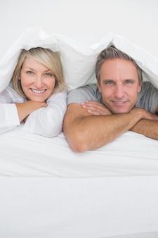 Couple attrayant souriant sous les couvertures à la caméra