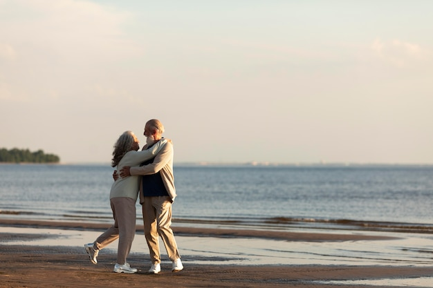 Couple au bord de la mer hugging full shot