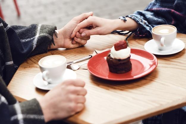 Couple au café main dans la main cupcake aux fraises.