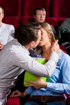 Couple au cinéma avec pop-corn s'embrasser
