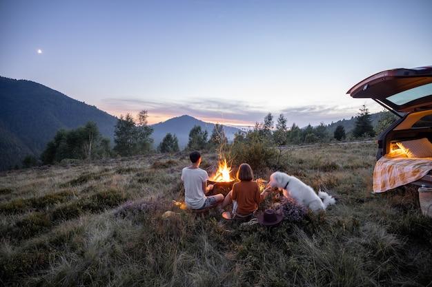 Couple au coin du feu au pique-nique en montagne