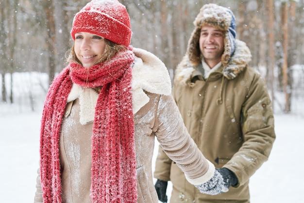 Couple au combat de boule de neige dans la forêt