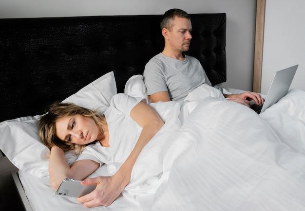Couple au lit à l'aide d'appareils