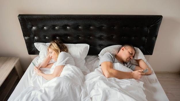 Couple au lit dos à dos à l'aide de mobiles