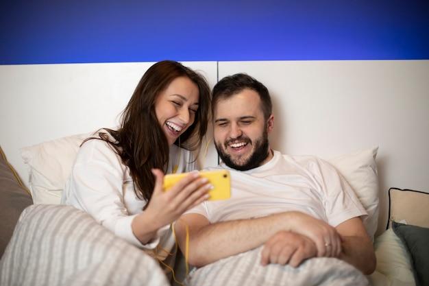 Couple au lit regarde smartphone