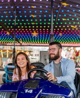 Couple au parc d'attractions s'amusant avec des autos tamponneuses