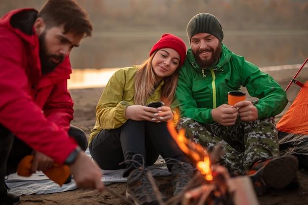 Couple au repos près d'un feu de camp avec un ami