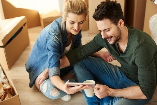 Couple autour de cartons avec tablette numérique