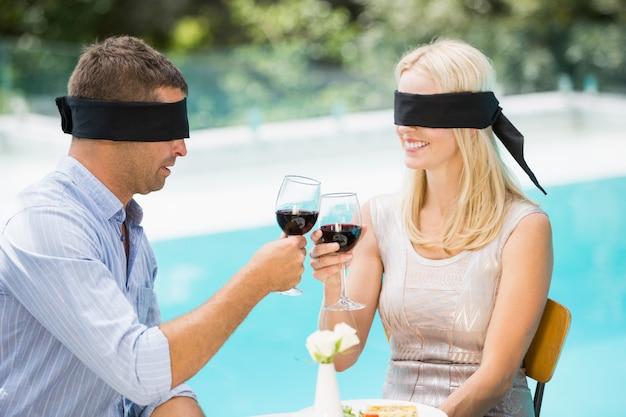 Couple aux yeux bandés portant un toast au vin rouge