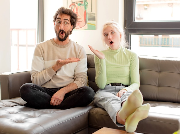 Couple ayant l'air surpris et choqué, avec la mâchoire tombée tenant un objet avec une main ouverte sur le côté