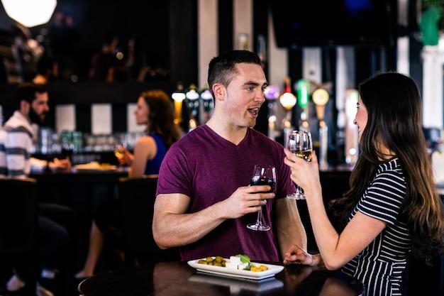 Couple ayant un apéritif avec du vin dans un bar