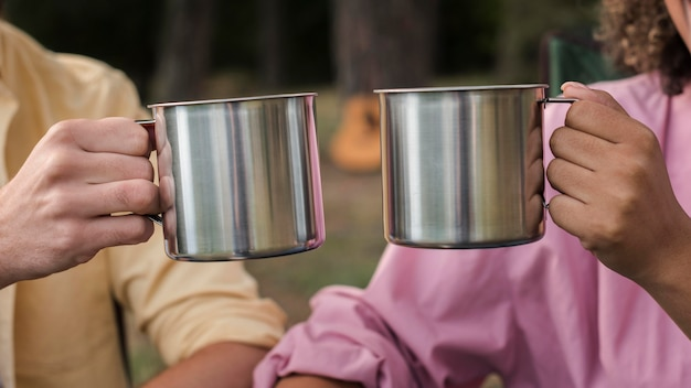 Couple ayant des boissons chaudes en camping en plein air