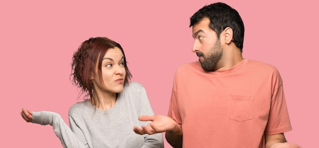 Couple ayant des doutes sur fond rose isolé