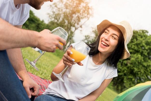 Couple ayant du jus d'orange sur une couverture de pique-nique