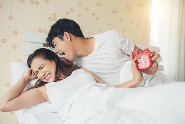 Couple ayant du mal à se lever tôt le matin sur le lit