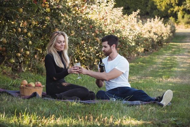 Couple ayant du vin dans un verger de pommiers