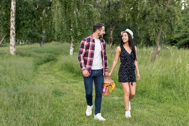 Couple ayant une promenade tenant un panier de pique-nique