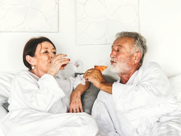 Couple ayant un prosecco au lit