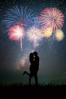 Couple ayant un temps romantique au fond de la nuit est la voie lactée et étoiles et feu d'artifice