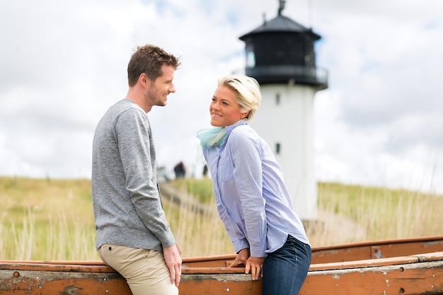Couple ayant des vacances romantiques dans les dunes de la plage de la mer du nord allemande en face du phare
