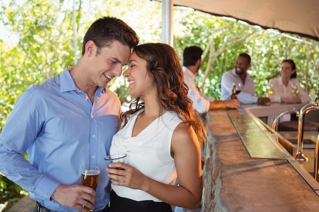 Couple ayant un verre de bière au comptoir au restaurant