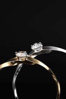Couple de bague en or et en argent diamant isolé sur fond noir rendu 3d