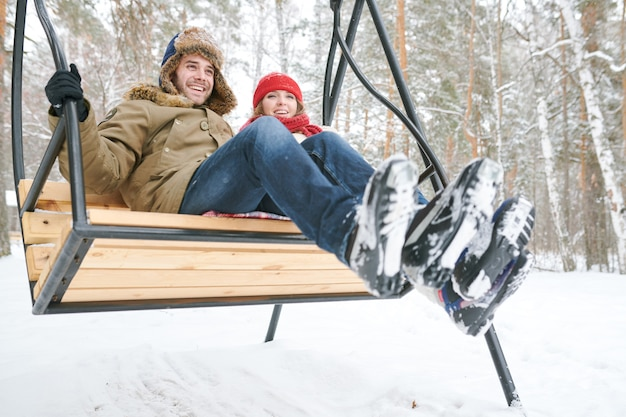 Couple sur balançoire en bois
