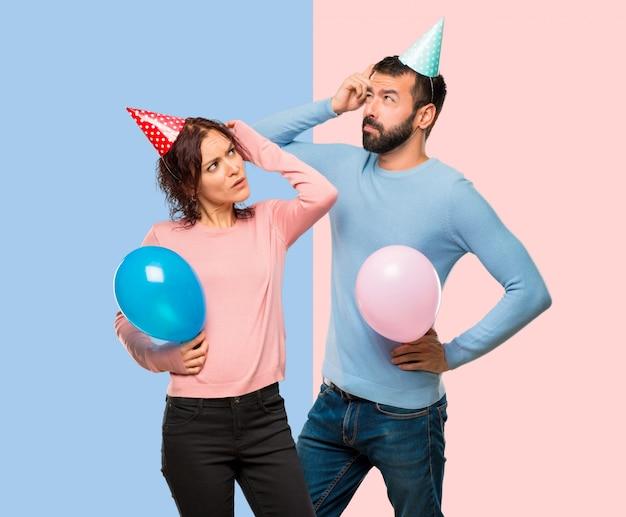 Couple, à, ballons, et, chapeaux anniversaire, avoir, doutes, et, confondre, figure, pendant, gratter