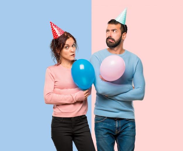 Couple avec des ballons et des chapeaux d'anniversaire ayant des doutes et avec une expression du visage confuse