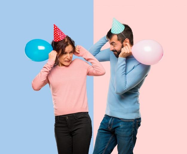 Couple avec des ballons et des chapeaux d'anniversaire couvrant les oreilles avec les mains