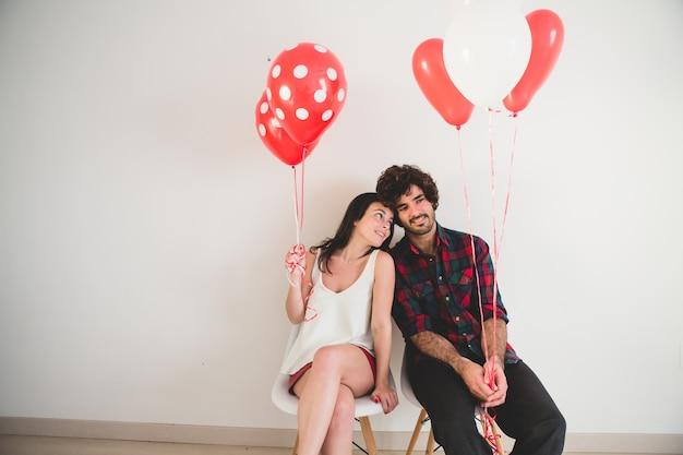 Couple avec des ballons dans les mains assis sur des chaises blanches