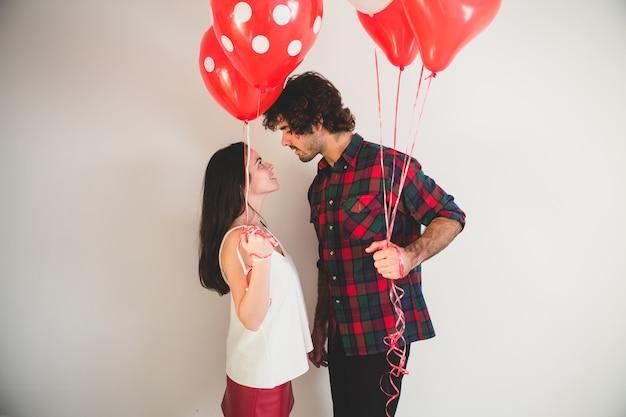 Couple avec des ballons dans les mains en regardant les uns les autres