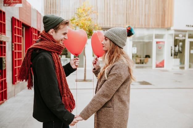 Couple avec des ballons dans la rue