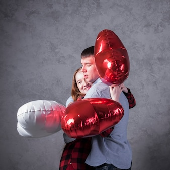 Couple avec des ballons en forme de coeur étreignant