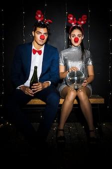 Couple avec bandeaux en bois de cerf et nez rigolo avec bouteille et boule disco