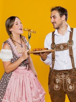 Couple bavarois essayant des saucisses allemandes