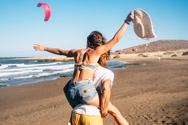 Couple de beaux adultes se fiancent et se marient ensemble à la plage - femme sur les épaules de l'homme le regardant et souriant