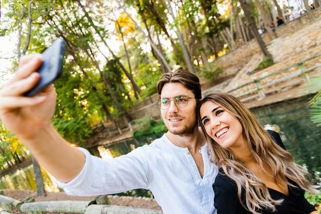 Couple de beaux jeunes mannequins posant candid tout en faisant un selfie avec leur téléphone.
